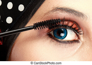 Woman applying mascara - close up portrait of beautiful ...