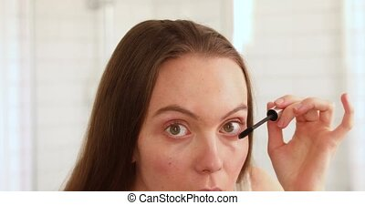 Woman applying mascara eyelash mirror
