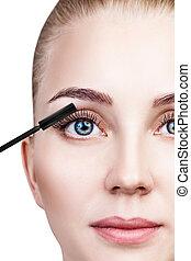 Woman applying mascara on eyelashes with brush.