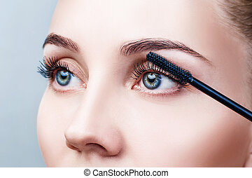 Woman applying mascara on eyelashes with brush.