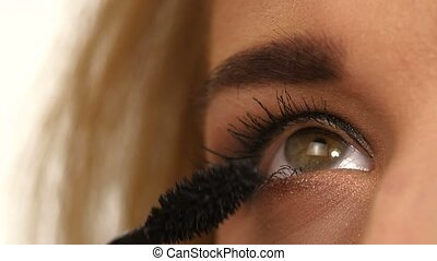 Woman applying mascara on her long eyelashes. close up