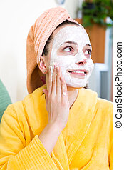 Woman applying mask to her face