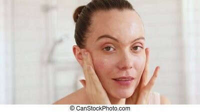 Woman applying moisturiser to her face in mirror - Close...