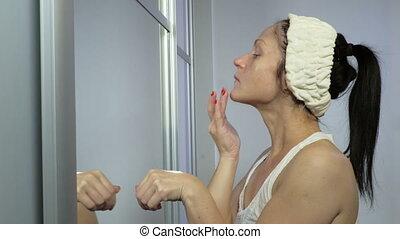 Woman applying moisturizer after Beauty Skin Care procedure