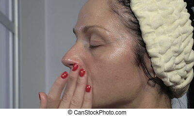 Woman applying moisturizer before Skin Care procedure