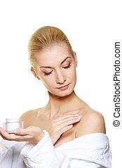 Woman applying moisturizer cream on her body
