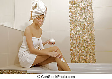 Woman applying moisturizer cream on the legs - Attractive...