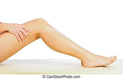 Woman applying body cream on her leg isolated on white.