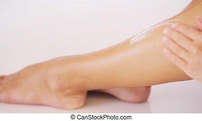 woman applying moisturizing cream to her leg - people,...