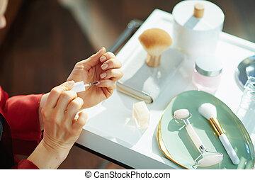 woman applying nail polish at home in sunny day