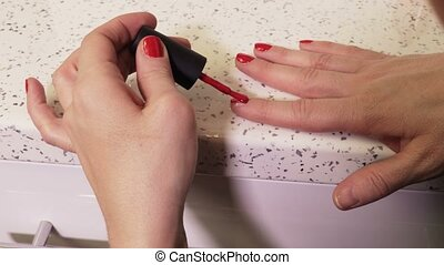 Woman applying nail polish back view