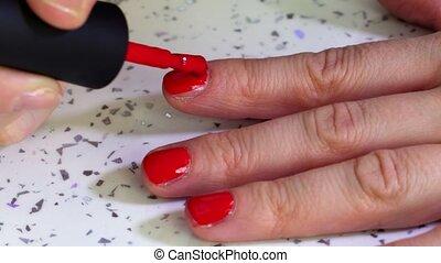Woman applying nail polish close up