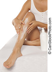 Woman applying protective cream after waxing