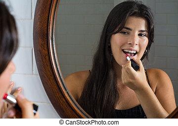 Woman applying red lipstick in bathroom.