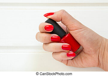 Woman applying red nail polish manicure. Female hand