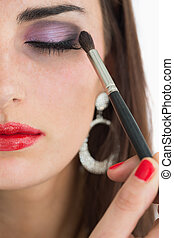 Woman applying smoky eyes - Woman with red lips applying ...