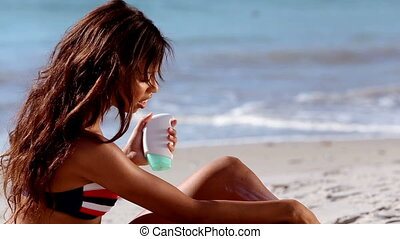 Woman applying sun cream on the beach