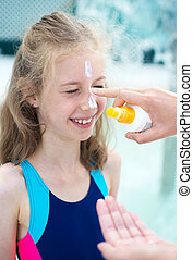 Woman applying sunblock cream on daughter's face.