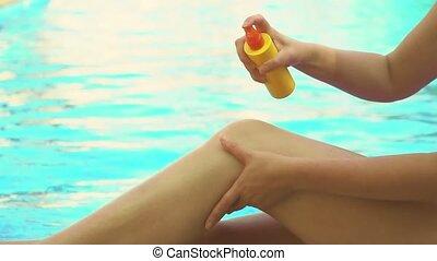 Woman applying sunblock cream on her legs.
