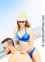 Woman applying sunscreen on the back of her man