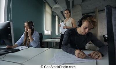 Woman approaches man at computer and explains his work beside a woman talking on headset and typing on a keyboard.