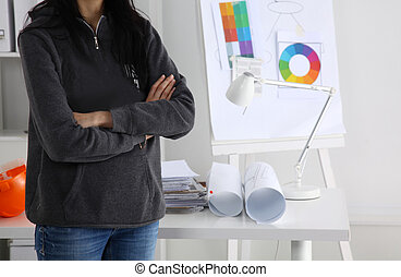 Woman architect standing with crossed arms in office