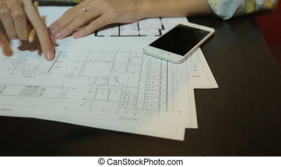 Woman architect working with blueprint sheets, layouts and drawings of the premises.