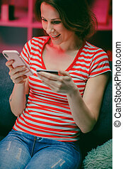 Woman are buying online with a credit card and smile while sitting on the sofa at home. Woman are using smart phone and doing online transactions, Past the internet