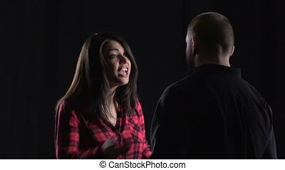 Woman arguing with her boyfriend on black background. Slow motion
