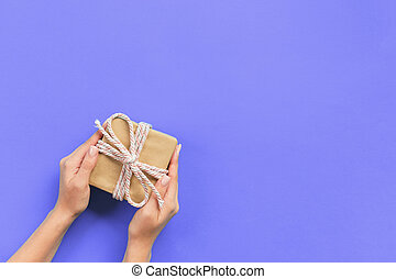 Woman arms holding gift box with pink ribbon on purple background, top view