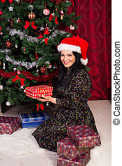Woman arrange Xmas gifts near tree
