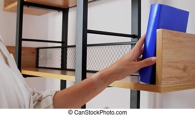 woman arranging books on shelving at home - home improvement...
