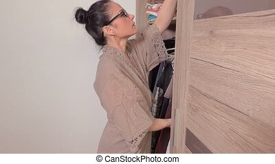 Woman arranging clothes in wardrobe