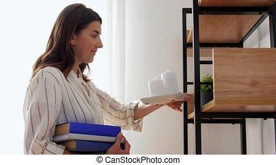 woman arranging flower, candles and books at home - home ...
