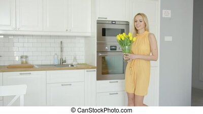 Woman arranging vase with flowers on table