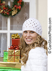 woman arriving at christmas party laden with gifts.