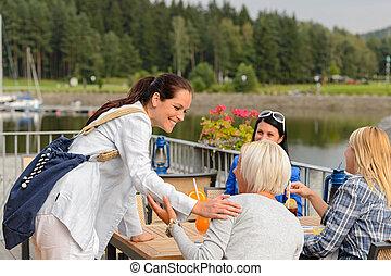 Woman arriving outdoor restaurant terrace friends - Woman ...