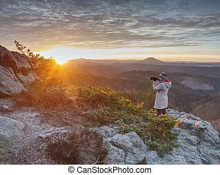 Woman art photographer works at camera on fiber tripod