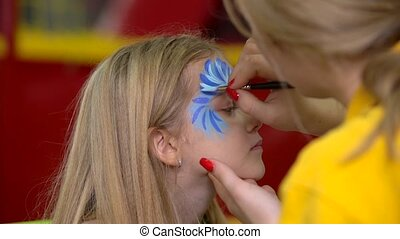 Woman artist drawing face painting to little girl. Close-up motion.