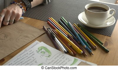 Woman artist draws illustrations for a children's book with pencils.