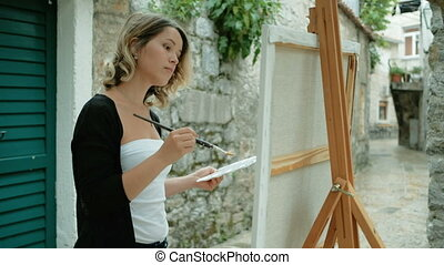 Woman artist draws painting from life on easel outdoors....