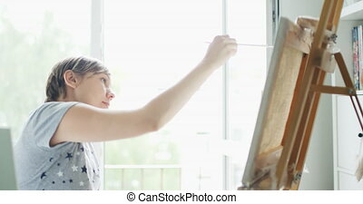Woman artist draws picture on canvas in home studio