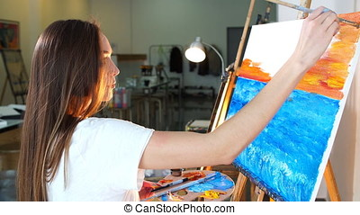 Woman artist following her inspiration painting her new...