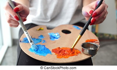 Woman artist mixing oil colours on palette holding in her...