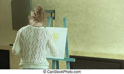 Woman artist on an easel draws a flower beside a butterfly...