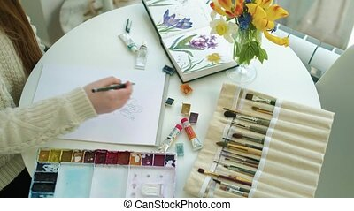 Woman artist painting watercolor paints