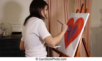 woman artist painting - woman painting a big red heart on...
