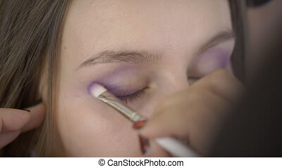 Woman artist puts shadow on eyes of client in beauty salon....
