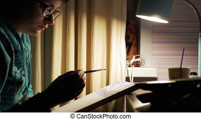 Woman Artist Sitting at a Table Draws a Picture at Home....