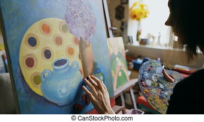Woman artist smearing oil paints on canvas picture in art...